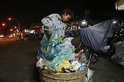A girl recycling worker sifts through the garbage on the street looking for materials to recycle, Phnom Penh. Rural peasants who have left the countryside in search of earning a decent living often end up as recycling workers on Phnom Penh's city streets. They earn a few dollars a day from selling by weight the plastic bottles, aluminium cans and cardboard they collect during a days work. Usually they work from the mid afternoon until midnight, sorting through the rubbish on the streets. They take what they collect to small sorting houses on the edge of the city.
