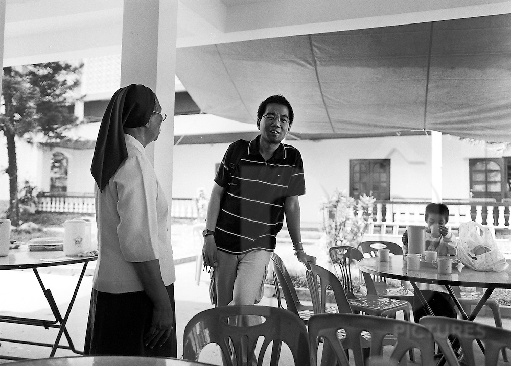 A man is talking with a nun in the yard of a church in Vientiane, Laos, Asia