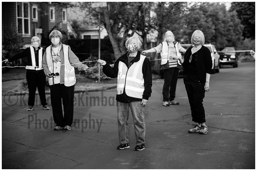 A women's walking group measures off enough social distance before starting their weekly walks together during the Covid19 pandemic in Portland, OR. They used measuring tape and electric extension cords to measure accurately. (names available)