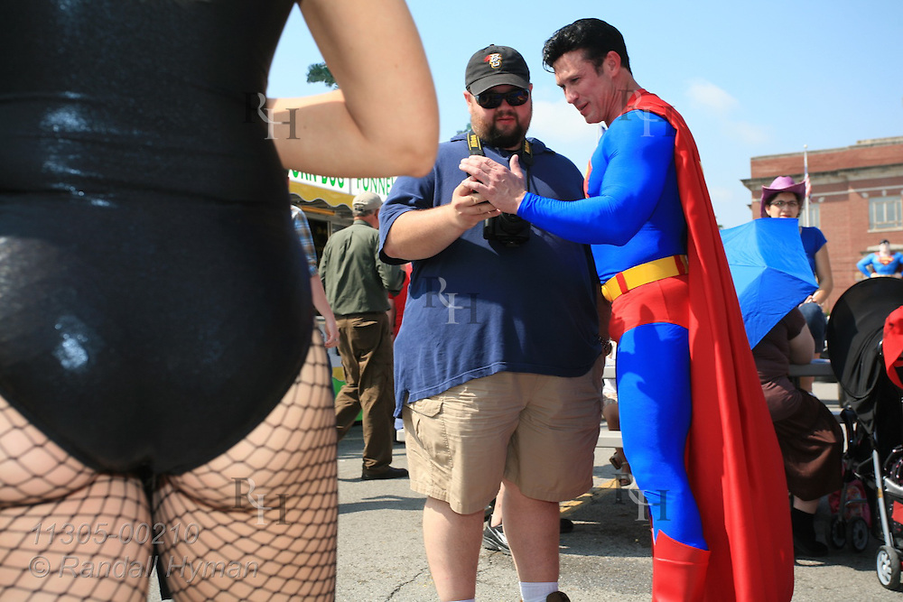 Superman devotee, Danny Kelley, dresses the part while mixing with crowds and looking at man's cell phone photo of him at Superman Celebration; Metropolis, Illinois.