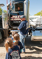 Jim Phelps helps Elm Street School Kindergarteners take a seat in the oil truck and sound the horn during Wednesday's field trip to Foley Oil in Belmont.    (Karen Bobotas/for the Laconia Daily Sun)