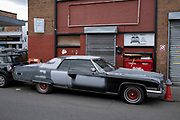 Vintage American car outside a garage in Deritend on 3rd August 2021 in Birmingham, United Kingdom. In this area of Birmingham there are lots of garages and breakers yards with lots of old cars in pieces parked on the street.