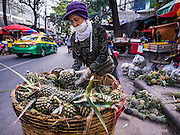 12 JANUARY 2017 - BANGKOK, THAILAND: A woman sorts pineapple on the street in front of Bo Bae Market. Bo Bae Market is a sprawling wholesale clothing market in Bangkok. There are reportedly more than 1,200 stalls selling clothes made in Thailand and neighboring countries. Bangkok officials have threatened to shut down parts of Bo Bae market, but so far it has escaped the fate of the other street markets that have been shut down.          PHOTO BY JACK KURTZ