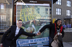 © Licensed to London News Pictures. 24/02/2016. Willesden, UK. Two campaigners join hands outside Willesden Magistrates Court in London where they and 11 other members of activist group Plane Stupid appeared charged with trespassing on the north runway at Heathrow Airport whilst protesting against a third runway.   Photo credit: Denis McWilliams/LNP