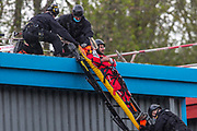 """Leicester, United Kingdom, May 24, 2021: Police protestor removal crew arrived at the building of the Israeli-owned Elbit-Thale subsidiary UAV Tactical Systems after it has been occupied for six consecutive days by the """"Palestine Action"""" activists' group. Both remaining activists were removed from the rooftop and arrested (in picture), meanwhile local communities' have organised a barricade and appear to be determined to not let the police leave the area with activists. """"Shut Elbit Down"""", """"Free! Free! Palestine"""" are among the slogans local residents are shouting. (Photo by Vudi Xhymshiti)"""
