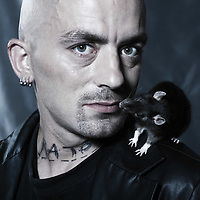 portrait studio on isolated background of a strange punk man portrait kissing  mouse rodent rat
