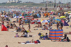 © Licensed to London News Pictures. 17/07/2021. Bridlington, UK. Sun-seekers make the most of the sunshine on Bridlington beach. Photo credit: Ioannis Alexopoulos/LNP