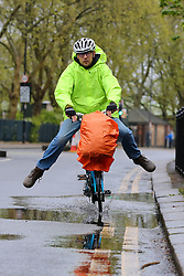 © Licensed to London News Pictures. 08/05/2021. London, UK. A cyclist rides through a puddle following heavy rainfall overnight in north London. More rain is forecasted for the South East of England today. Photo credit: Dinendra Haria/LNP