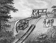 Inclined plane powered by water wheel in use on a canal.  The inclined plane was used to transfer vessels, in this case tub boats, from one level of a canal to another and was an alternative to a lock.  The example shown was considered suitable for smaller canals with rise of 20-30 feet (6-9m). From 'A Treatise on the Improvement of Canal Navigation'  Robert Fulton, (London 1796). Engraving.