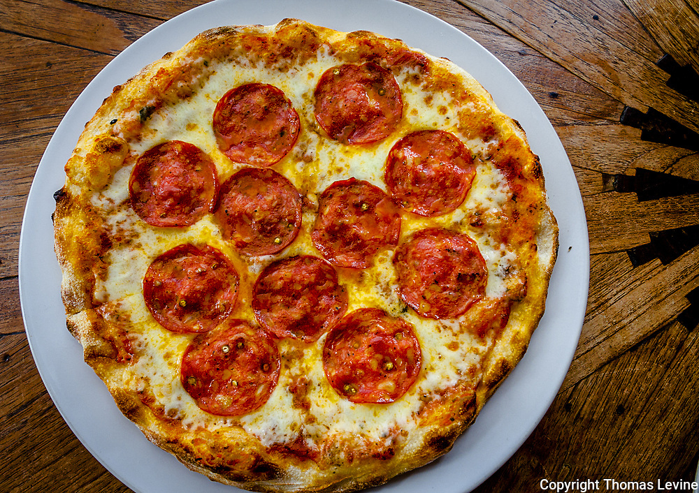 Round whole pepperoni pizza served on a plate sitting on a wood grained table