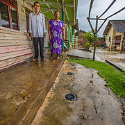 CAPTION: Romlah and Ilyas stand outside their house, next to three biopores they installed after receiving training from the Biopores Centre. LOCATION: Langkapura Village, Bandar Lampung, Indonesia. INDIVIDUAL(S) PHOTOGRAPHED: Ilyas (left) and Romlah (right).