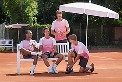 Group of young men relaxing on tennis court, Bavaria, Germany
