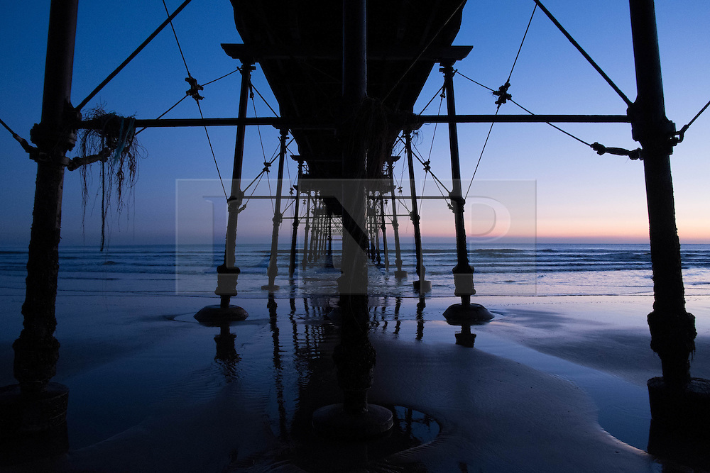 © Licensed to London News Pictures. 12/03/2014<br /> <br /> Saltburn, Cleveland, United Kingdom<br /> <br /> The Victorian pier in Saltburn, Cleveland is bathed in the first light of dawn.<br /> <br /> Photo credit : Ian Forsyth/LNP
