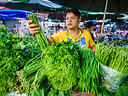 20 JUNE 2018 - BANGKOK, THAILAND: A produce vender at Makkasan Market, a small local market in central Bangkok. Officials in Thailand are wrestling with Thais use of plastic bags. The issue became a very public one in early June when a whale in Thai waters died after ingesting 18 pounds of plastic. In a recent report, Ocean Conservancy claimed that Thailand, China, Indonesia, the Philippines, and Vietnam were responsible for as much as 60 percent of the plastic waste in the world's oceans.     PHOTO BY JACK KURTZ