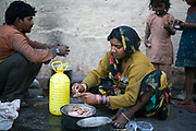 A homeless family and their children cook by the side of the road at a temporary shelter in Karol Bagh, New Delhi, India