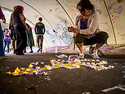 21 APRIL 2017 - CHANHASSEN, MN: A woman lights a candle at a memorial to Prince in the pedestrian tunnel in front of Paisley Park, his former home and recording studio. The tunnel has become a memorial to Prince, people have drawn graffiti in the tunnel honoring him and they leave memorials in the tunnel. The superstar died from an accidental overdose of the opioid fentanyl on April 21, 2016. Friday was the first anniversary of his death. Crowds of people gathered at Paisley Park, which is now a museum, to honor the Minnesota born musician.     PHOTO BY JACK KURTZ