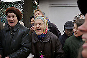 Moscow, Russia, 10/04/2004..Russian Orthodox Easter celebrations at the Church of Peter and Paul in central Moscow. Women laugh and shout as they are blessed with holy water by Father Vasily..