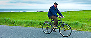Local Irish man cycling traditional bicycle along country lane in County Clare, West of Ireland
