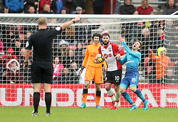Southampton's Charlie Austin (centre) and Arsenal's Nacho Monreal collide during the Premier League match at St Mary's Stadium, Southampton.