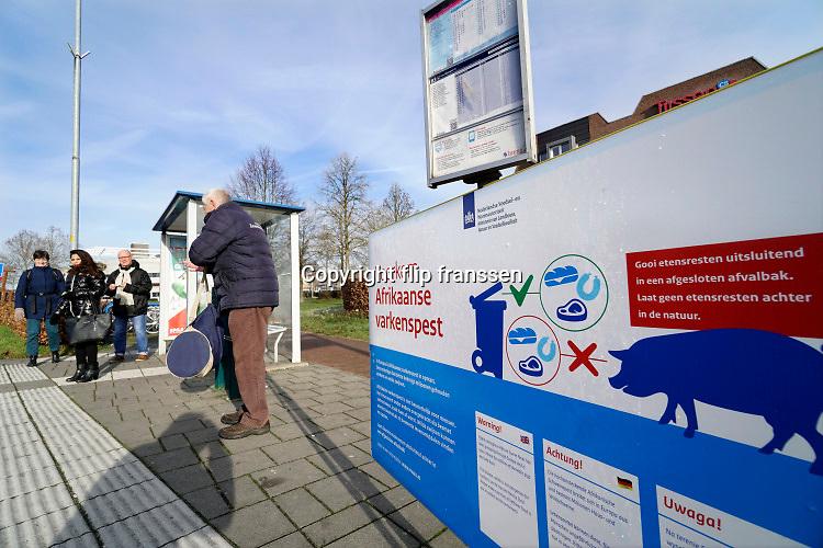 Nederland, Malden, 20-1-2019 Langs de weg bij een bushalte in het landelijk gebied, platteland, staat een waarschuwingsbord tegen de afrikaanse varkenspest, een zeer besmettelijke en fatale ziekte voor varkens die in Belfie gesignaleerd is. Het bord staat in het grensgebied met Duitsland . De tekst is ook in het Pools vanwege de mensen uit Polen die hier in de regio werken .Foto: Flip Franssen