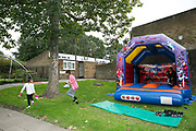 Children play on a bouncy castle during a TRA, Tenants and residents association, community day at Cressingham Gardens estate on 9th September 2015 in South London, United Kingdom. Cressingham Gardens is a council garden estate, located on the southern edge of Brockwell Park. It comprises of 306 dwellings and built to the design of Lambeth Borough Council architect Edward Hollamby in the early 1970s. In 2012, Lambeth Council proposed regeneration of the estate, a decision highly opposed by many residents. Since the announcement, the highly motivated campaign group Save Cressingham Gardens has been active.