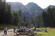 Polish hikers rest on seats and benches on the footpath leading towards the climb up to Sarnia Skala, a mountain in the Tatra National Park, on 16th September 2019, near Koscielisko, Zakopane, Malopolska, Poland.