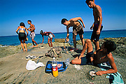 With a friend, the Costa grandsons, Javier (with snorkel) and Ariel (prone), spend the day fishing with snorkels and spear guns at the Havana shore, ten minutes by bike from home. Ariel cleans the catch while cousin Javier and a friend put their gear down on the rocks. Hungry Planet: What the World Eats (p. 104).