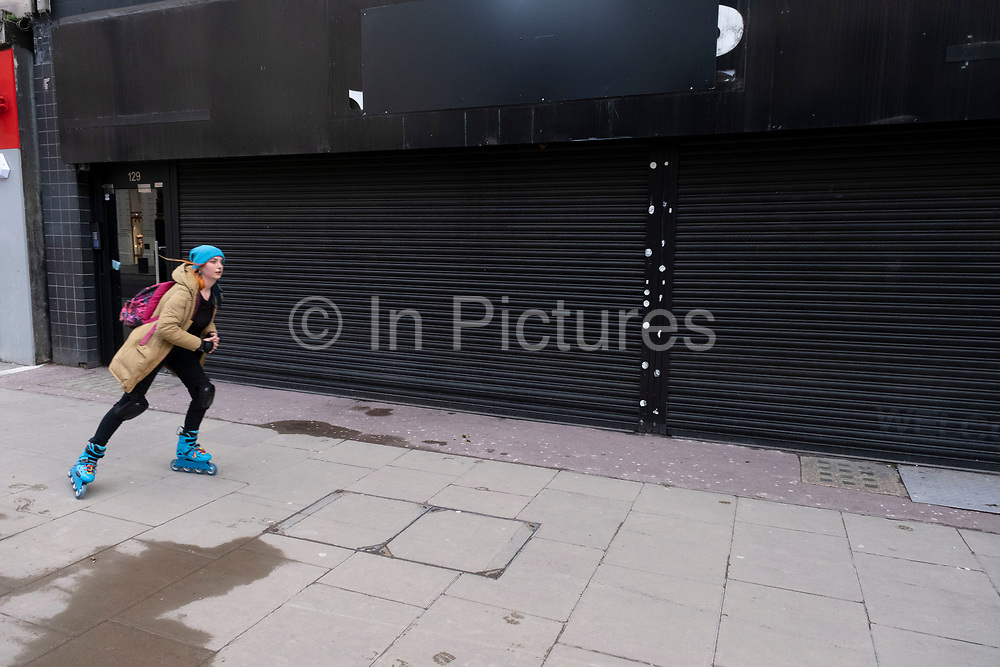 Woman rollerblades past shuttered closed shop along Oxford Street which is largely empty of shoppers as the national coronavirus lockdown three continues on 28th January 2021 in London, United Kingdom. Following the surge in cases over the Winter including a new UK variant of Covid-19, this nationwide lockdown advises all citizens to follow the message to stay at home, protect the NHS and save lives.