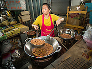 02 SEPTEMBER 2015 - BANGKOK, THAILAND: A vendor fries peanuts in a wok in Bang Chak Market. The Bang Chak Market serves the community around Sois 91-97 on Sukhumvit Road in the Bangkok suburbs. About half of the market has been torn down, vendors in the remaining part of the market said they expect to be evicted by the end of the year. The old market, and many of the small working class shophouses and apartments near the market are being being torn down. People who live in the area said condominiums are being built on the land.         PHOTO BY JACK KURTZ