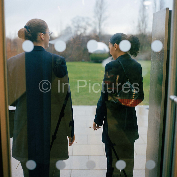 Receptionists, Charlene Cassell and Tracey Cook  left taking a smoking break at their office in  Glaxo Smith Kline, Brentford. From the series Desk Job, a project which explores globalisation through office life around the World.