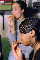 Teenage girls eating pizza,