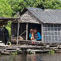 A woman and her child waving to our boat as we passed by their floating house.