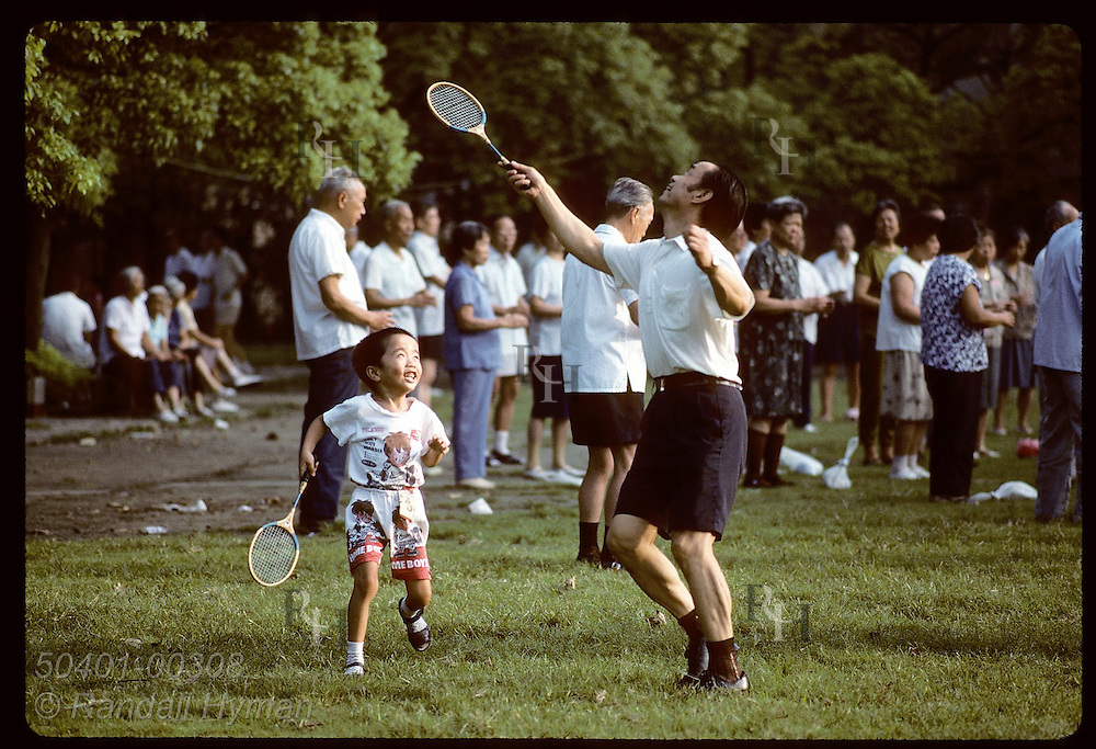 Father and son chase after badminton birdie with rackets in Jin An Park; sunrise in Shanghai. China