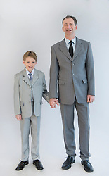 Father and son holding hands, smiling, portrait