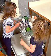 Sisters loading dishwasher after lunch ages 5 and 3.  WesternSprings  Illinois USA