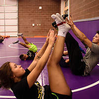 Alias Starkovich doing toe touches with his students at the Morningside Wrestling Camp at Miyamura High School, Tuesday July 25. Starkovich brought the camp to Gallup because he wanted to give back to the wrestling program and community here.