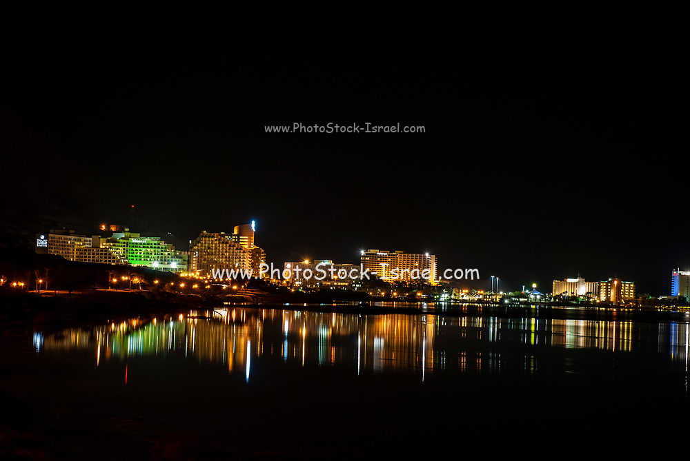 Night shot of the illuminated Hotels, with light reflecting in the Dead Sea, Ein Bokek, Israel as seen from south