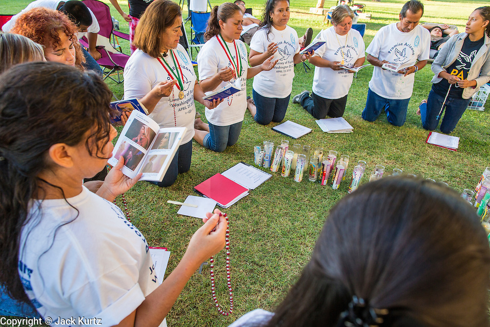 25 JUNE 2012 - PHOENIX, AZ:  Immigration activists pray at the Arizona State Capitol in Phoenix, AZ, Monday before the US Supreme Court ruled on Arizona's immigration law, SB1070. The lawsuit, US v. Arizona, determines whether or not Arizona's tough anti-immigration law, popularly known as SB1070 is constitutional. Among other things, the law requires police officers to check the immigration status of anyone whom they arrest, allows police to stop and arrest anyone whom they believe to be an illegal immigrant, makes it a crime for someone to be in the state without valid immigration papers, and makes it a crime to apply for or hold a job in Arizona without proper papers. The federal government sued Arizona because it believes the law is invalid because it is trumped by federal immigration laws. The court struck down most of the law but left one section standing, the section authorizing local police agencies to check the immigration status of people they come into contact with.   PHOTO BY JACK KURTZ