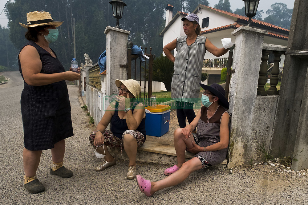 June 18, 2017 - Leiria, Portugal - Local residents wearing dust masks outside a home spared from the flames, after the deadly fire swept through the area. A raging forest fire in central Portugal killed at least 62 people as they desperately tried to flee, charring cars and trucks as it swept over roads. The disaster, the worst tragedy Portugal has experienced in decades shook the nation. (Credit Image: © Atlantico Press via ZUMA Wire)