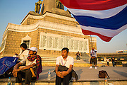 24 JANUARY 2014 - BANGKOK, THAILAND: An anti-government protestor waves the Thai flag on Victory Monument Shutdown Bangkok protest site. Shutdown Bangkok has been going for 12 days with no resolution in sight. Suthep Thaugsuban, the leader of the anti-government protests and the People's Democratic Reform Committee (PDRC), the umbrella organization of the protests,  is still demanding the caretaker government of Prime Minister Yingluck Shinawatra resign, the PM says she won't resign and intends to go ahead with the election.    PHOTO BY JACK KURTZ