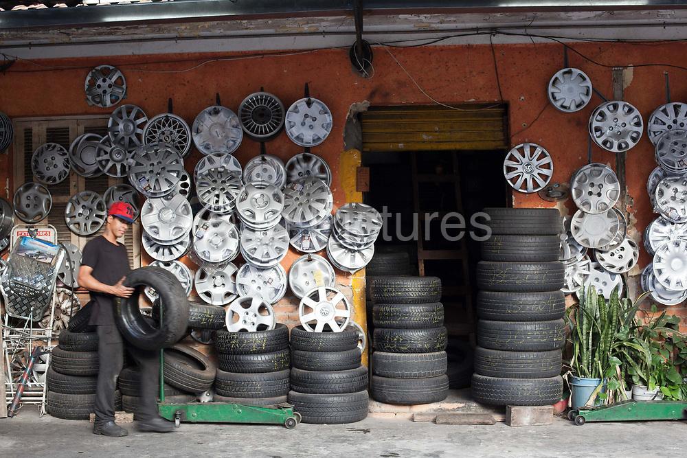 A young man carrying a tire in a colourful mechanics shop, Vila Madalena neighbourhood, Sao Paulo, Brazil.