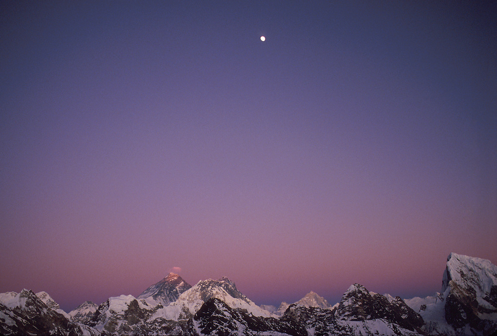 """Mount Everest, the earth's highest mountain, 8,848 metres (29,029 ft) above sea level, is tinged with the last rays of the setting sun as the moon rises high above the Kumbhu range. Makalu, world's 5th highest mountain, is at rear to the right, also tinged by sunlight.<br /> The Tibetans, who share this mountain with Nepal, refer to it as Chomolungma, or """"Holy Mother""""."""