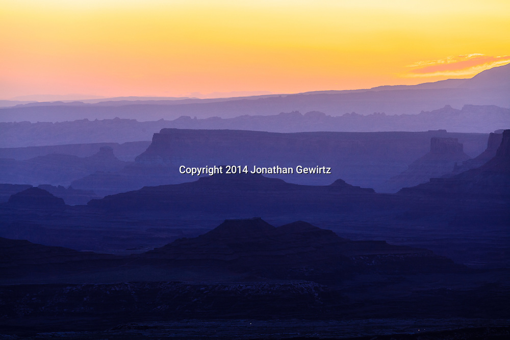 The brightening morning sky silhouettes distant ridges beyond Buck Canyon and the White Rim mesa in Canyonlands National Park, Utah.<br /> <br /> WATERMARKS WILL NOT APPEAR ON PRINTS OR LICENSED IMAGES.