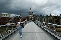 © Licensed to London News Pictures. 25/08/2020. LONDON, UK.  People cross the Millennium Bridge at lunchtime as Storm Francis arrives in the UK.  Following a morning of heavy rain, the afternoon is occasional sunshine and intermittent strong gusts of wind.  Photo credit: Stephen Chung/LNP