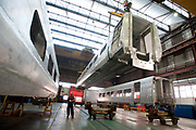 Workers moove a Pendolino carbodyshell  for Virgin  at the Alstom Ferroviaria SPA factory in Savigliano, Italy, on Friday, Feb. 11, 2011. Photographer: Victor Sokolowicz/Bloomberg