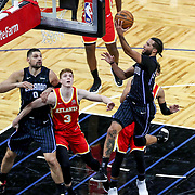 ORLANDO, FL - MARCH 03: Michael Carter-Williams #7 of the Orlando Magic drives to the net in front of Kevin Huerter #3 of the Atlanta Hawks and Nikola Vucevic #9 of the Orlando Magic during the first half at Amway Center on March 3, 2021 in Orlando, Florida. NOTE TO USER: User expressly acknowledges and agrees that, by downloading and or using this photograph, User is consenting to the terms and conditions of the Getty Images License Agreement. (Photo by Alex Menendez/Getty Images)*** Local Caption *** Michael Carter-Williams; Kevin Huerter; Nikola Vucevic
