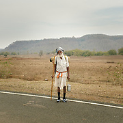 A Hindu pilgrim circumambulating the holy Naramda river. He carries water from the river in his tin can and all his belongings on his back.<br /> Madhya Pradesh Province.