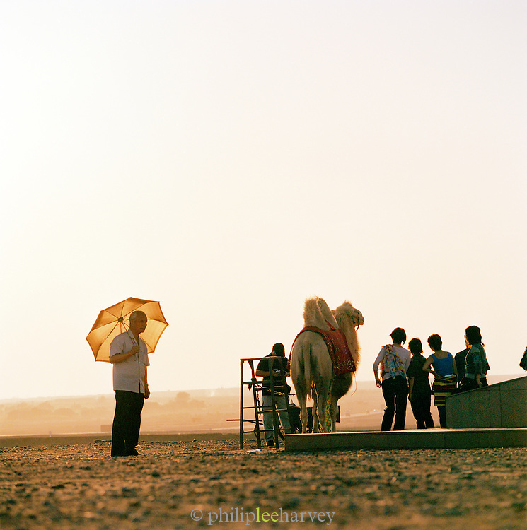 Tourists going for a camel ride in the desert near the Gaochang Mountains, dubbed the Flaming Mountains. In the autonomous region of Xinjiang, China