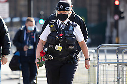 © Licensed to London News Pictures. 22/03/2021. London, UK. A police officer prepares to place a rose on the PC Keith Palmer memorial outside the Houses of Parliament. Today marks four years since the Westminster Bridge terror attack and a commemorative plaque is expected to be installed on Westminster Bridge when Coronavirus restrictions are lifted . Photo credit: George Cracknell Wright/LNP