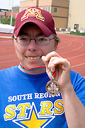 Proud track champion holding winning medal. Special Olympics U of M Bierman Athletic Complex. Minneapolis Minnesota USA